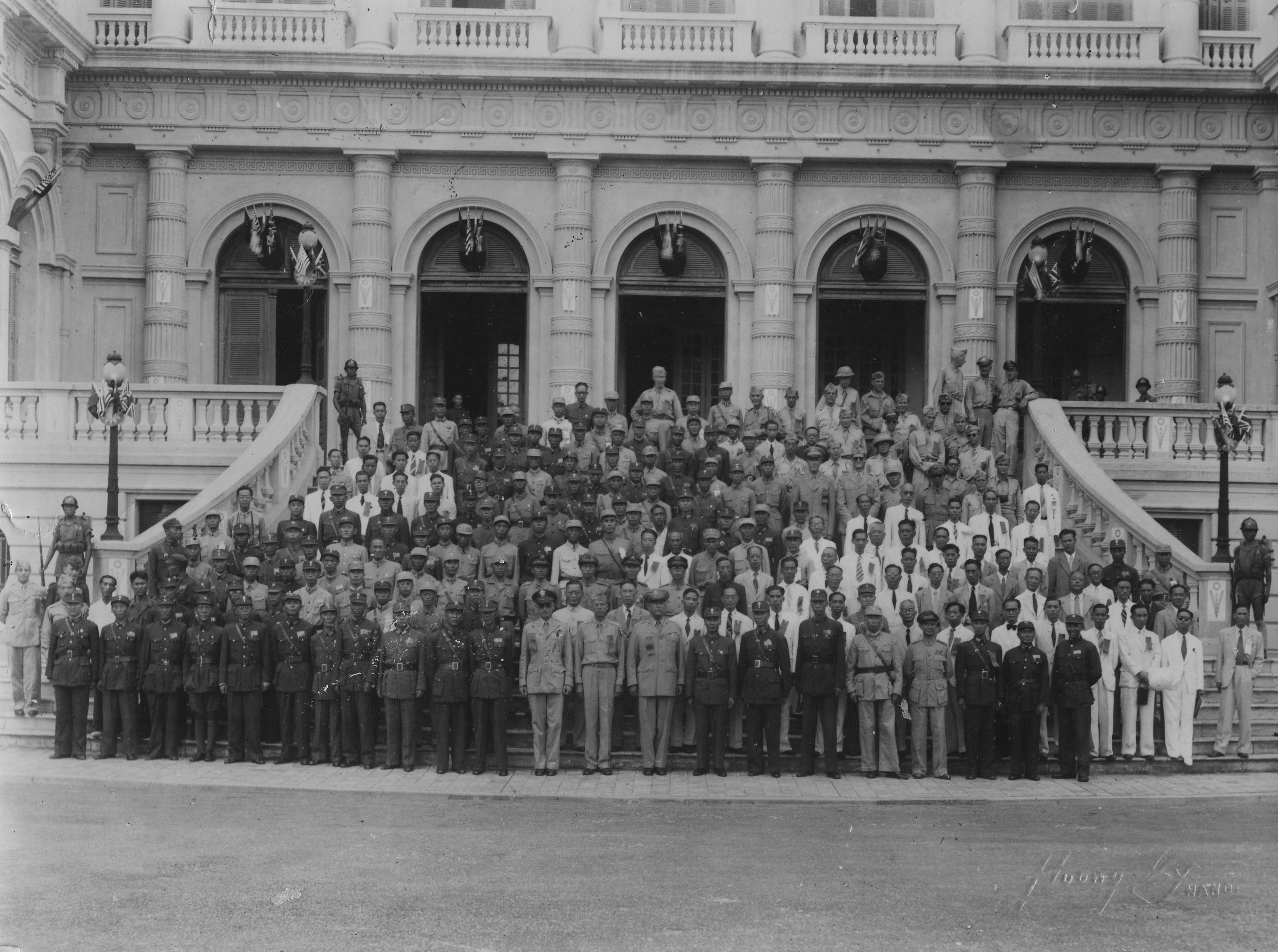 Image taken at the Governor General's Mansion in Hanoi, French Indochina, September 1945. Colonel Hutson poses with U.S., Chinese, and Vietnamese officials.